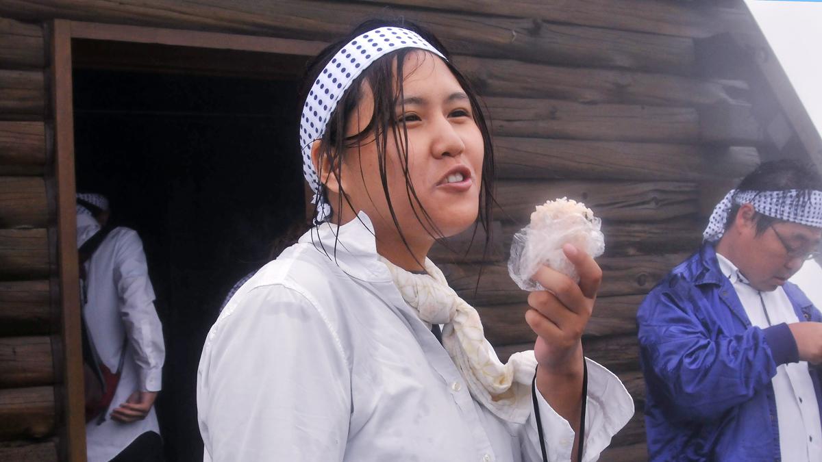 頂上の避難小屋の前で、おにぎりを頬張る女子学生