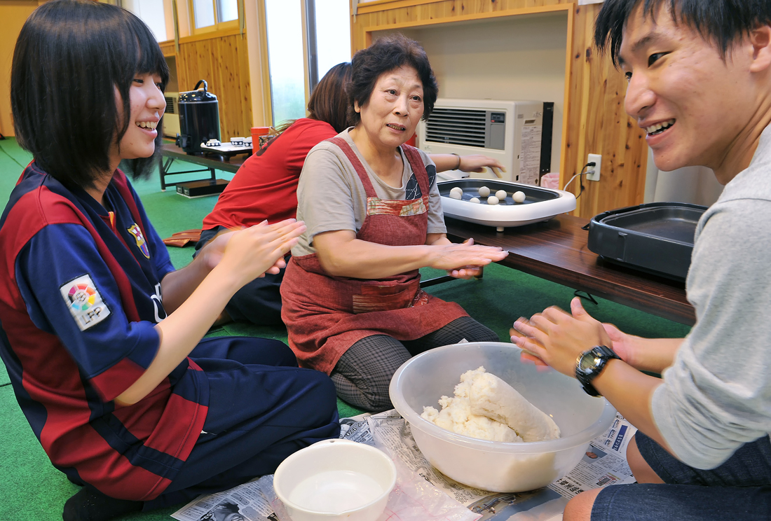 ダマコ作りを学生に指導する女集(中央)。大間越・スーパー主婦の一人