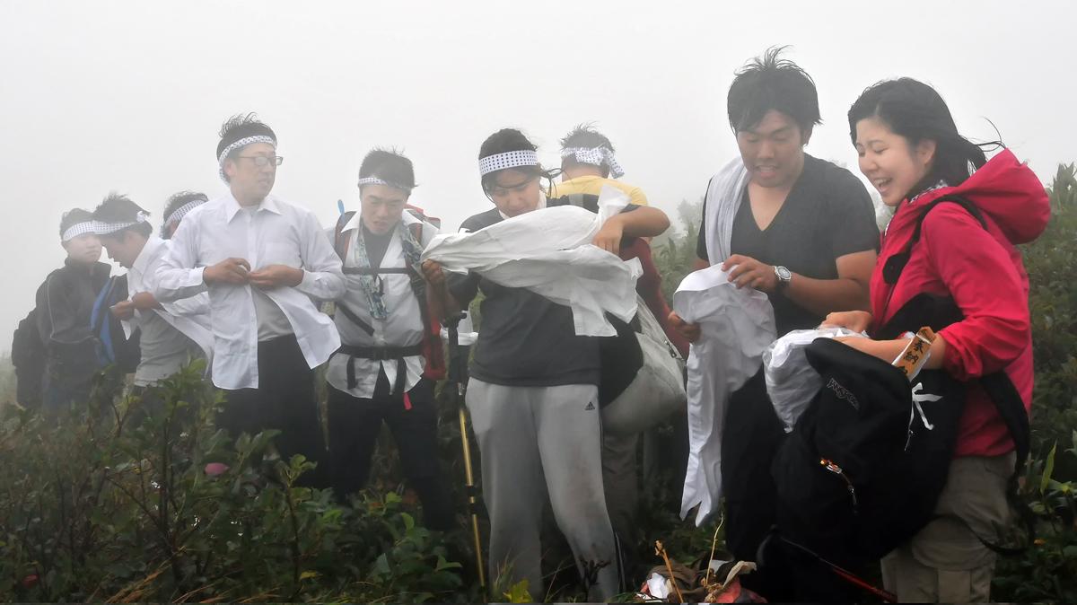 頂上に到着。強風の中、神事のために着替える学生たち