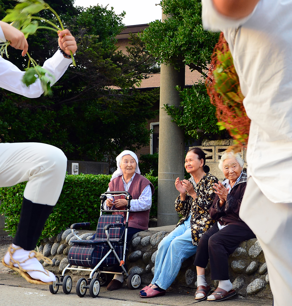 学生たちの踊りに笑顔で拍手を送るお年寄りたち