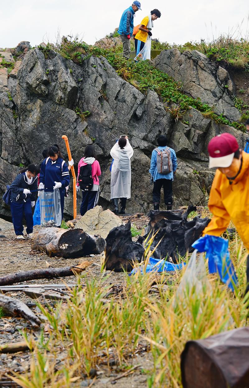 漂着ゴミで汚れた海岸の清掃に臨む