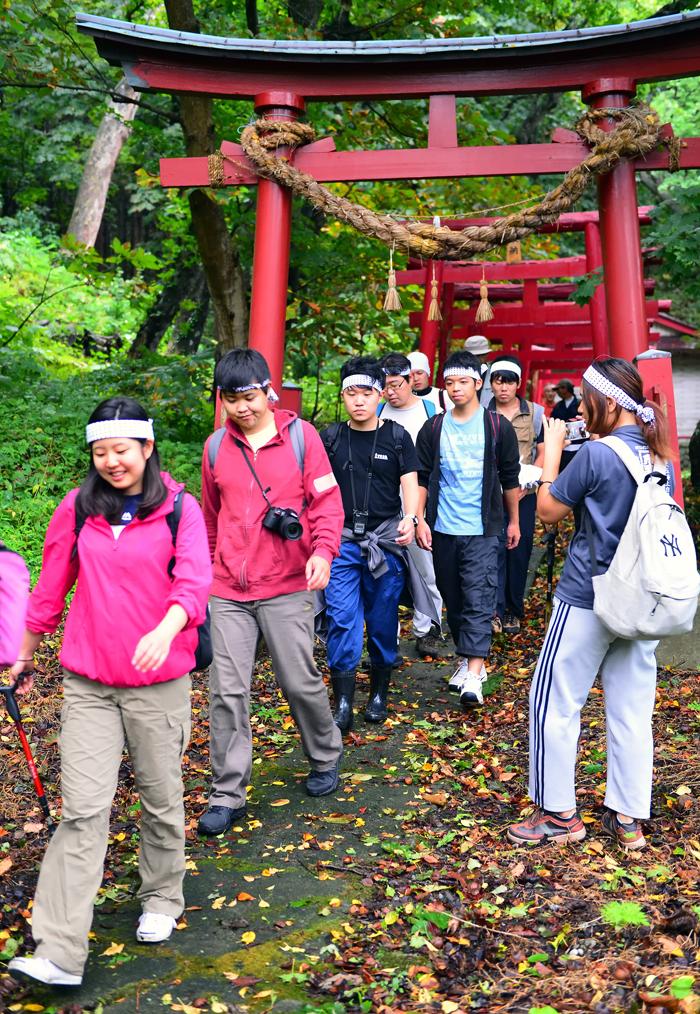 神社に祈願した後、山へ向かう学生たち