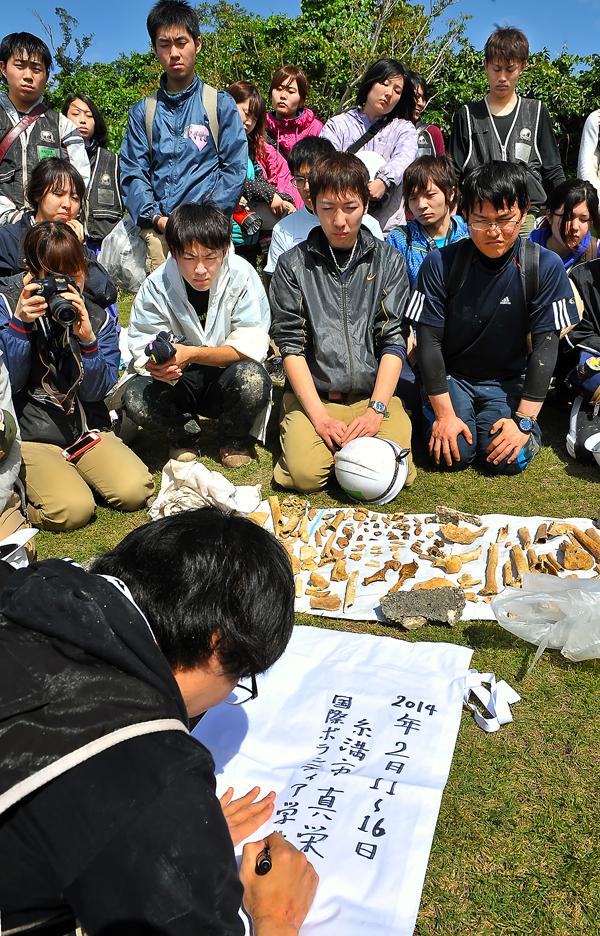 納骨袋へ遺骨を収容する学生