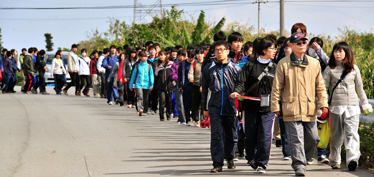 平良先生とサトウキビ畑を貫く道を歩く学生たち