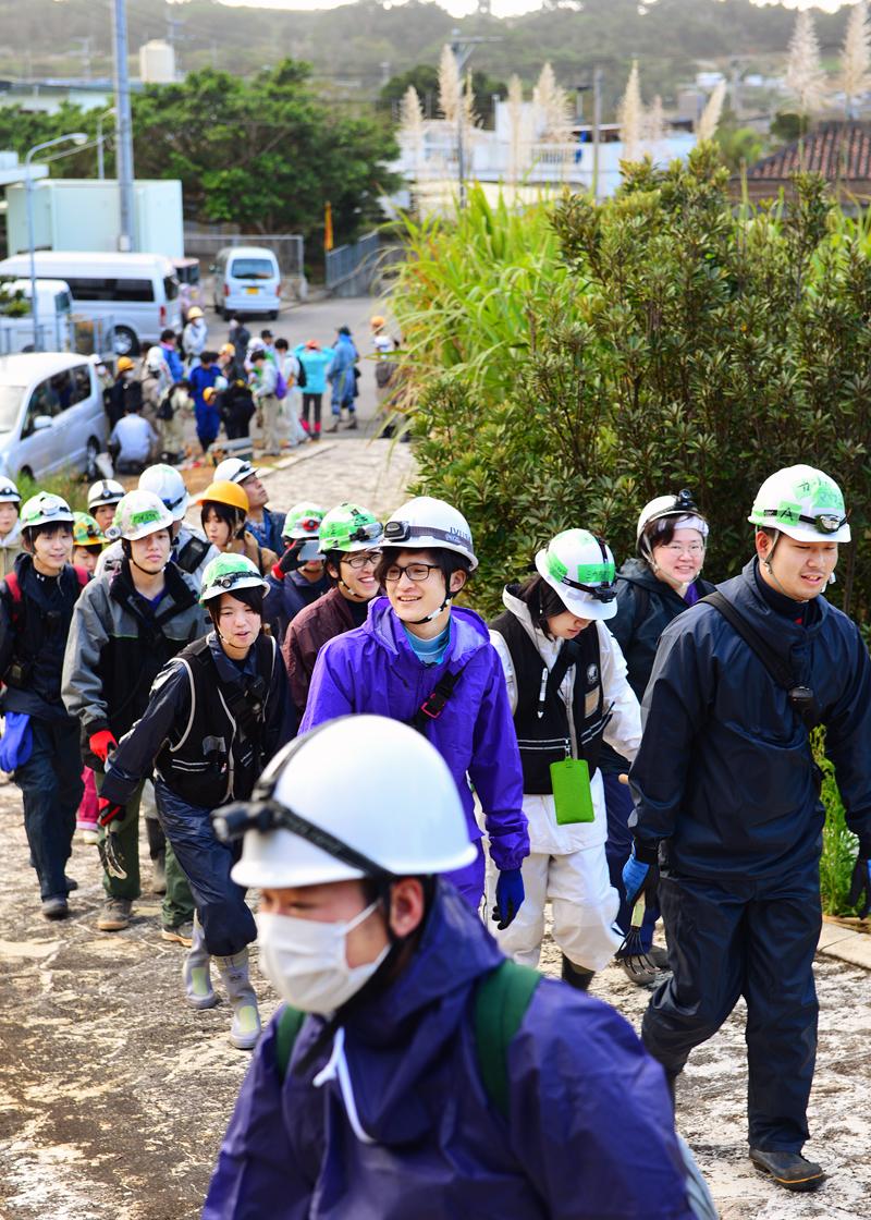 糸満市内の集落を背に、収集現場に向かう学生たち