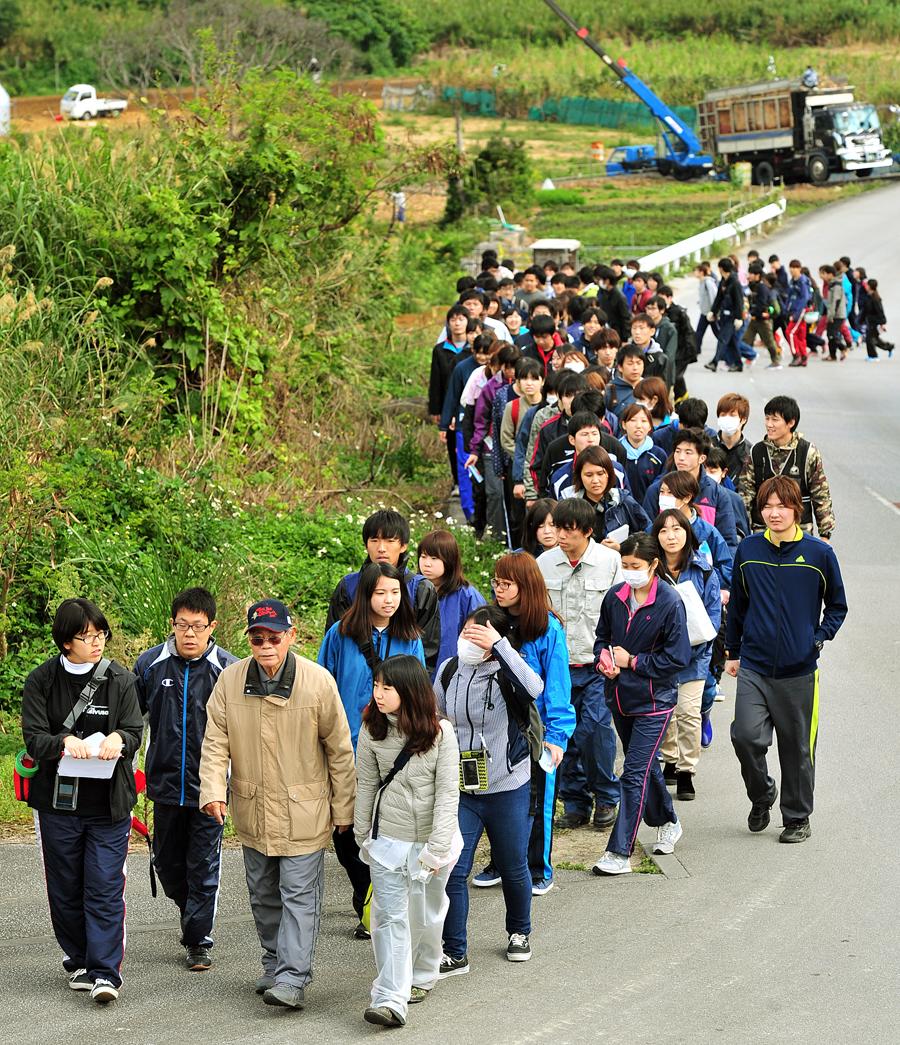 収穫が進むサトウキビ畑の横を歩く学生たち