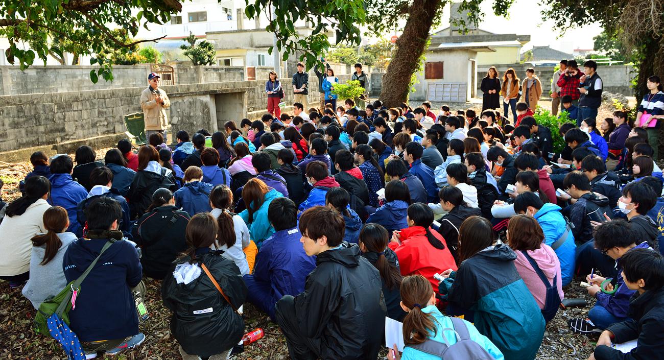 「全員死亡の家」の屋敷跡に座り込む学生たち