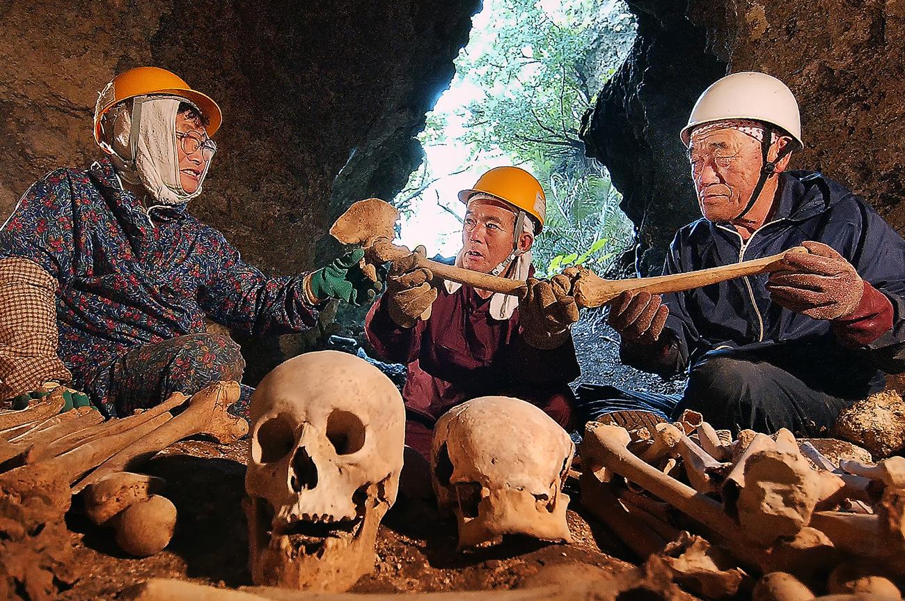 遺骨が並ぶ八重瀬の野戦病院壕で、井上さんご夫妻と語る国吉さん(中央)