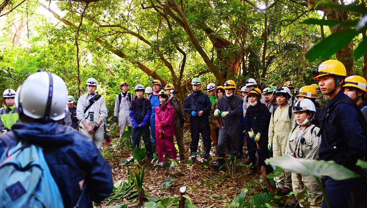 ジャングルの中で、活動前の注意事項を聞く学生たち