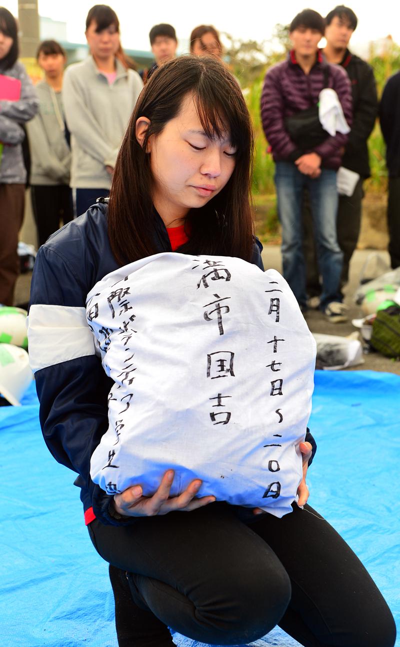 IVUSAが集めた遺骨が入った袋を抱え上げるリーダーの合原波穂さん