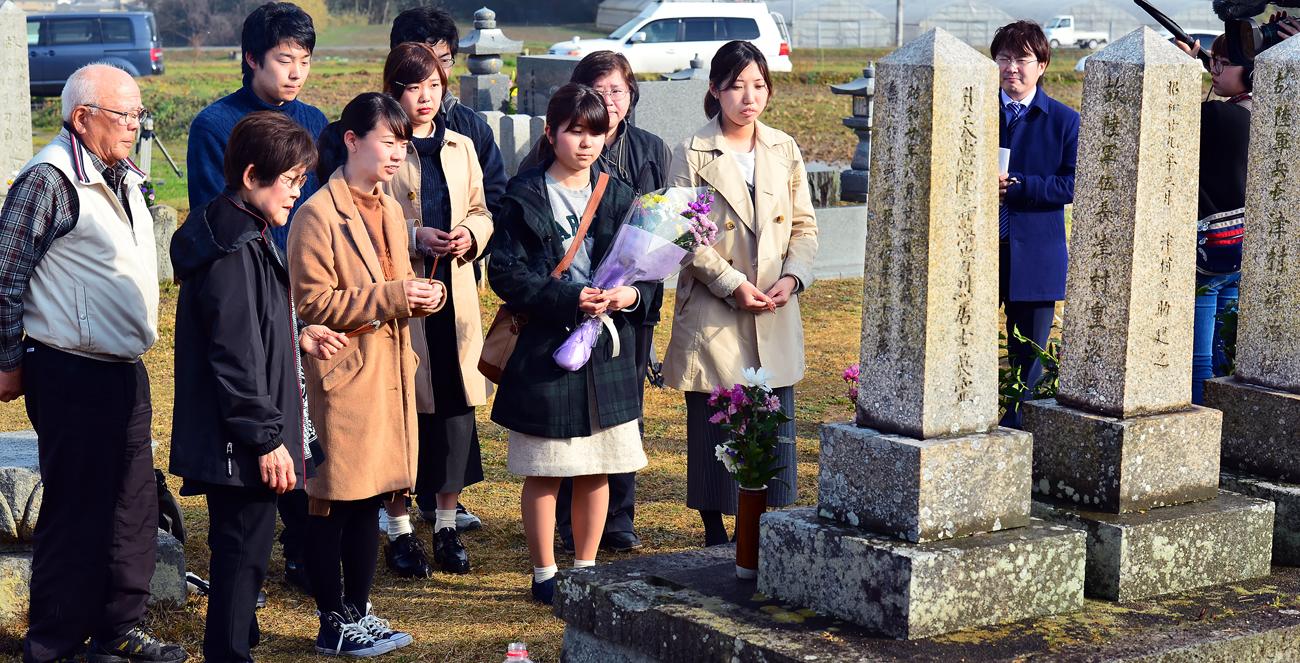 献花する学生を見守る慶子さんと良一さん(右端)