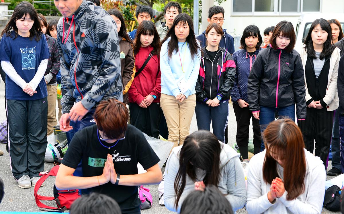 遺骨に手を合わせて祈る学生たち
