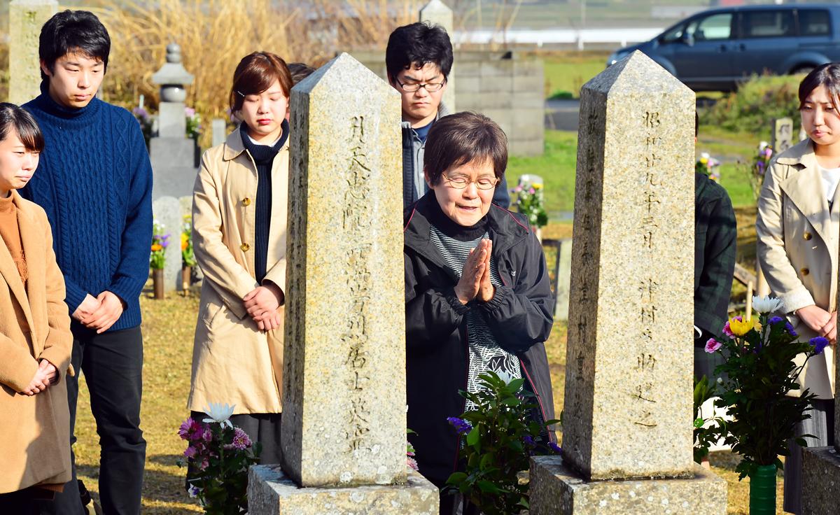父親の墓標に手を合わせながら語りかける慶子さん