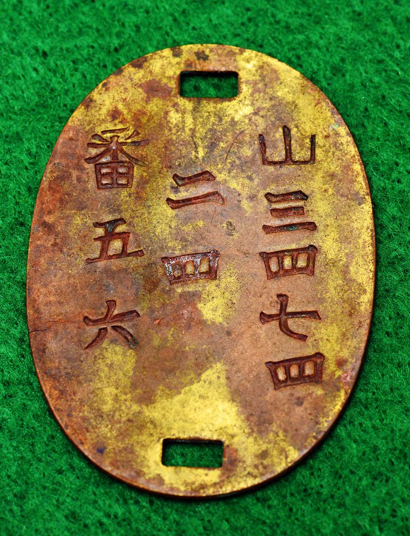岩の下から出てきた旧日本陸軍の認識票。歩兵22連隊の兵士の物