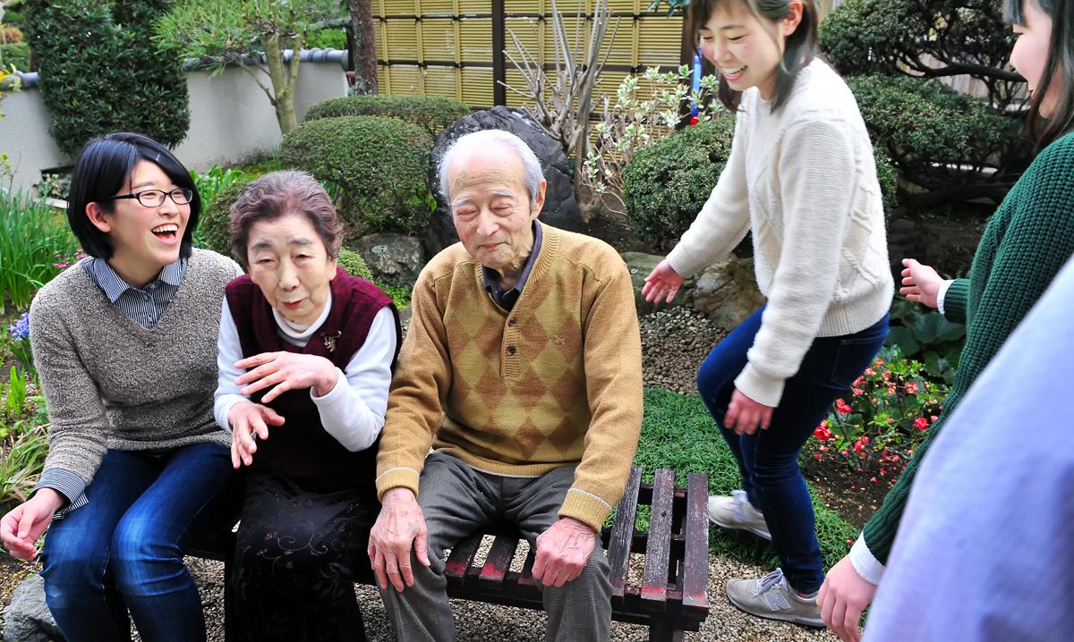 庭で学生たちとベンチに座られる伊東隊長と奥さま