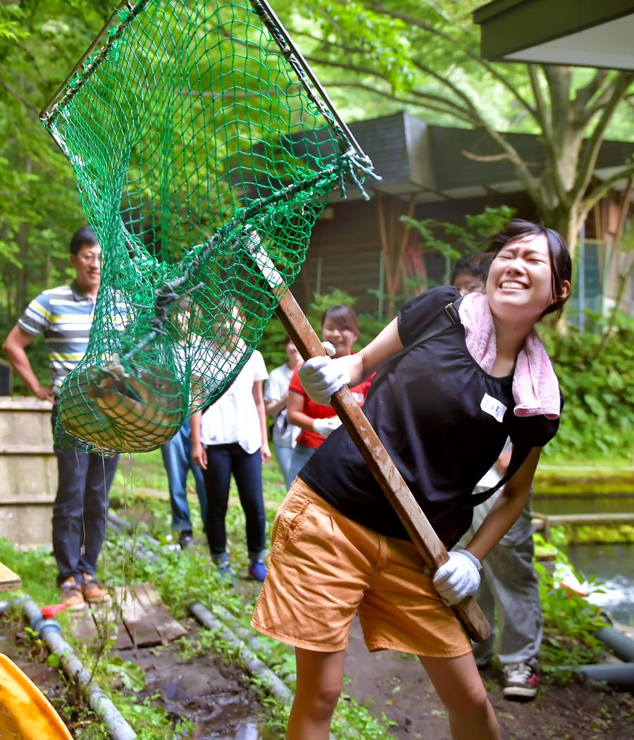 幻の淡水魚「イトウ」を網で掬いあげるリーダーの小嶋さん。「重ーい!」