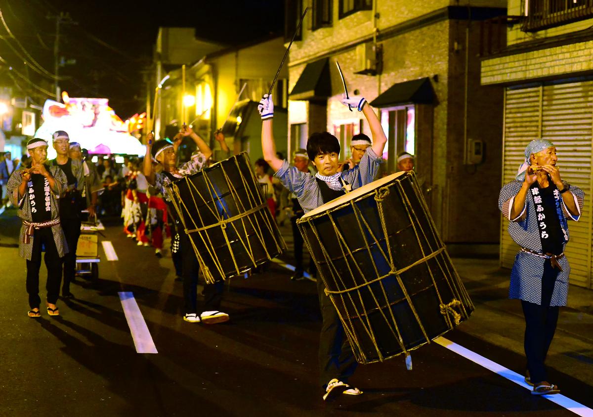力強い太鼓の打ち手たちが商店街を練る